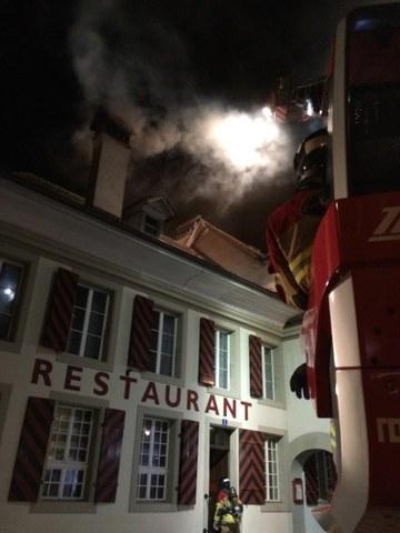 Starker Rauch auch im Bereich des Kamins; Feuerwehrmänner auf der Autodrehleiter zur Intervention bereit.