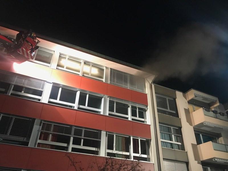 Die Feuerwehr verschafft sich über die Autodrehleiter Zugang zum vierten Stockwerk.