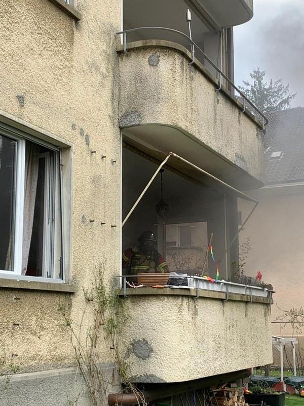 Feuerwehrmann mit Atemschutz auf dem Balkon der betroffenen Wohnung.