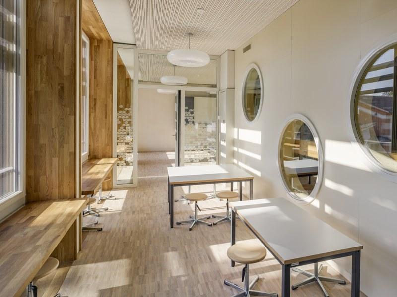Das Projektbild zeigt einen Flur mit Parkettboden, holzigen Schreibflächen am Fenster, runden Luken und zwei Pulten mit Stühlen.