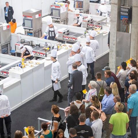 Impressionen von den SwissSkills 2018 in Bern: Köchinnen und Köche mit weissen Kopfbedeckungen tragen ihren Wettkampf vor einem grossen Publikum aus.. Vergrösserte Ansicht