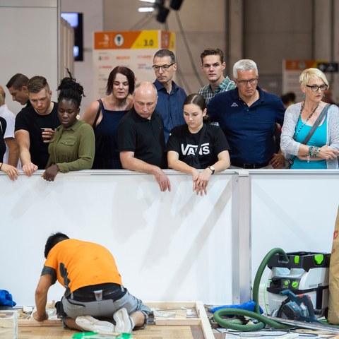 Impressionen von den SwissSkills 2018 in Bern: Zuschauerinnen und Zuschauer beobachten einen jungen Mann, der auf dem Boden kniend einen Wettkampf bestreitet.. Vergrösserte Ansicht