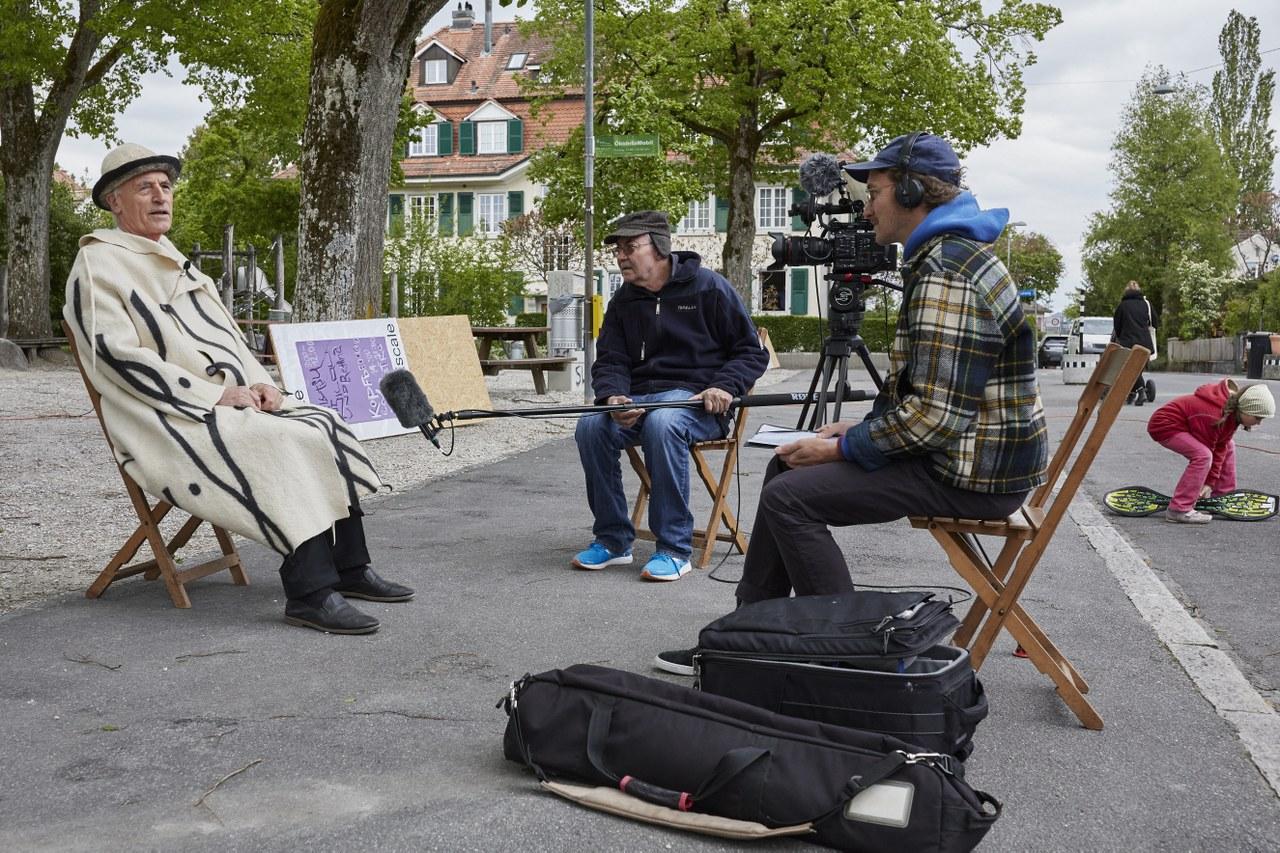 Das Bild zeigt einen älteren Herren im Mantel auf einem Klappstuhl auf einem öffentlichen Platz, der in ein Mikrofon erzählt.