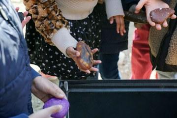 Kinder der HPS füllen den Grundstein mit bemalten Steinen (Bild Peter Brand). Vergrösserte Ansicht