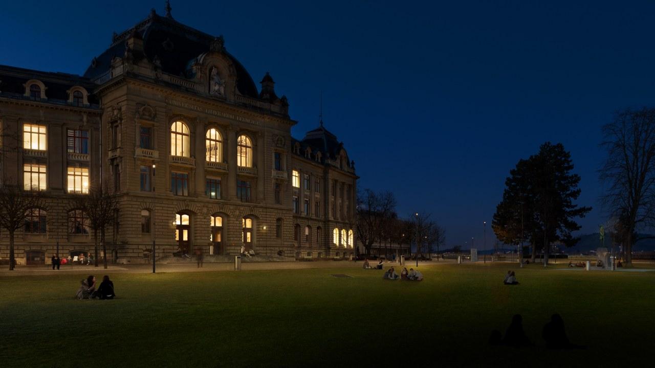 Das Bild zeigt das Hauptgebäude der Uni Bern bei Nacht, die Wiese mit sitzenden Menschen ist sanft beleuchtet.