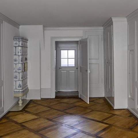 Rathausgasse 12: Gassenzimmer im zweiten Obergeschoss mit ursprünglicher Raumausstattung und Keramikofen von Peter Gnehm. (© Dominique Uldry). Vergrösserte Ansicht