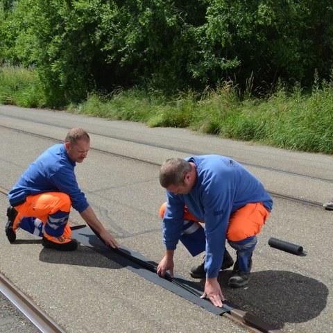 TDF, Einweihung Ziellinie, Arbeiter verlegen Schienenabdeckung. Vergrösserte Ansicht