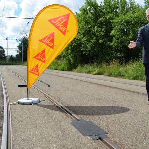 TDF, Einweihung Ziellinie, Hans Peter Wyss präsentiert Schienenabdeckung. Vergrösserte Ansicht