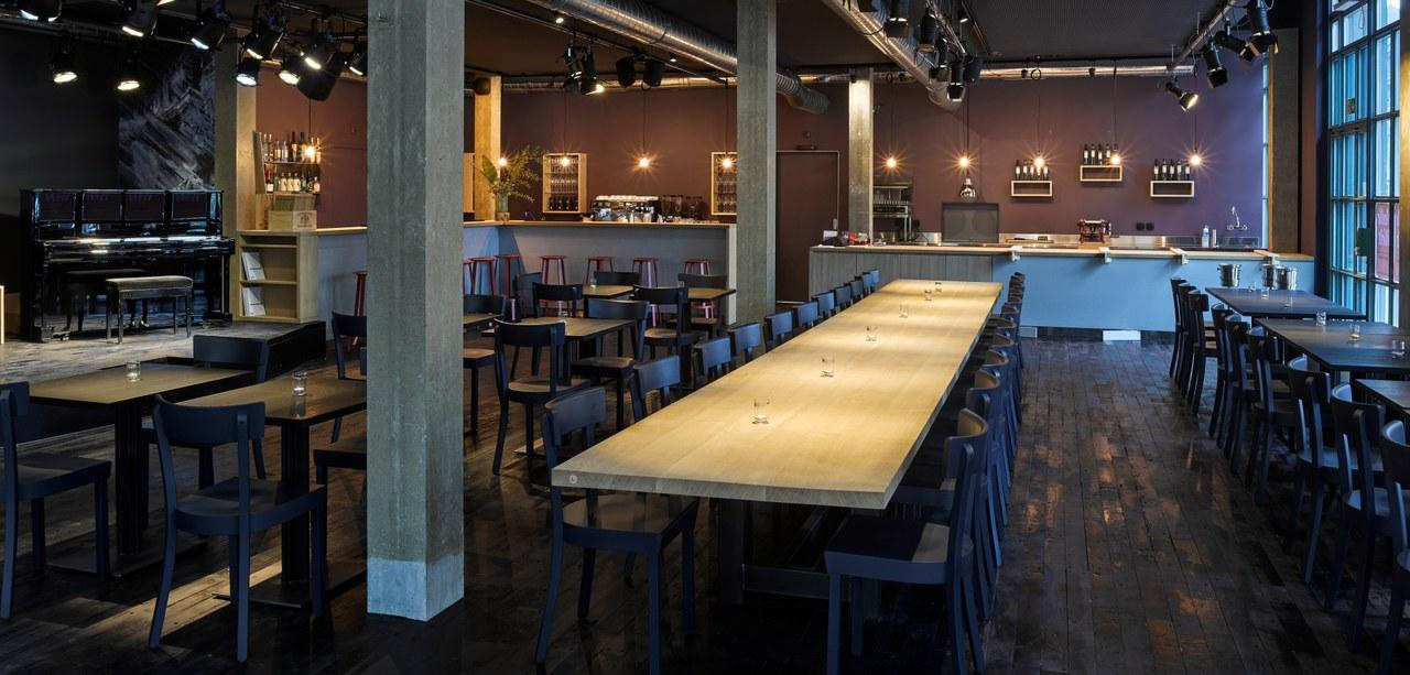 Das Bild zeigt einen Saal mit Betonpfeilern, hellen Holztischen, dunklem Riemenboden, ebenfalls dunklen Holzstühlen und weinroter Wandfarbe. Im Hintergrund sieht man die Bar, links steht ein Klavier.