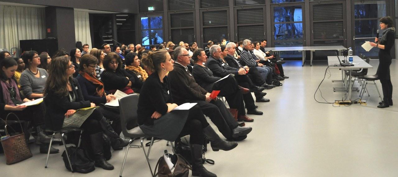Viele Personen in einem Saal, die einem Referat von Gemeinderätin Franziska Teuscher zuhören.