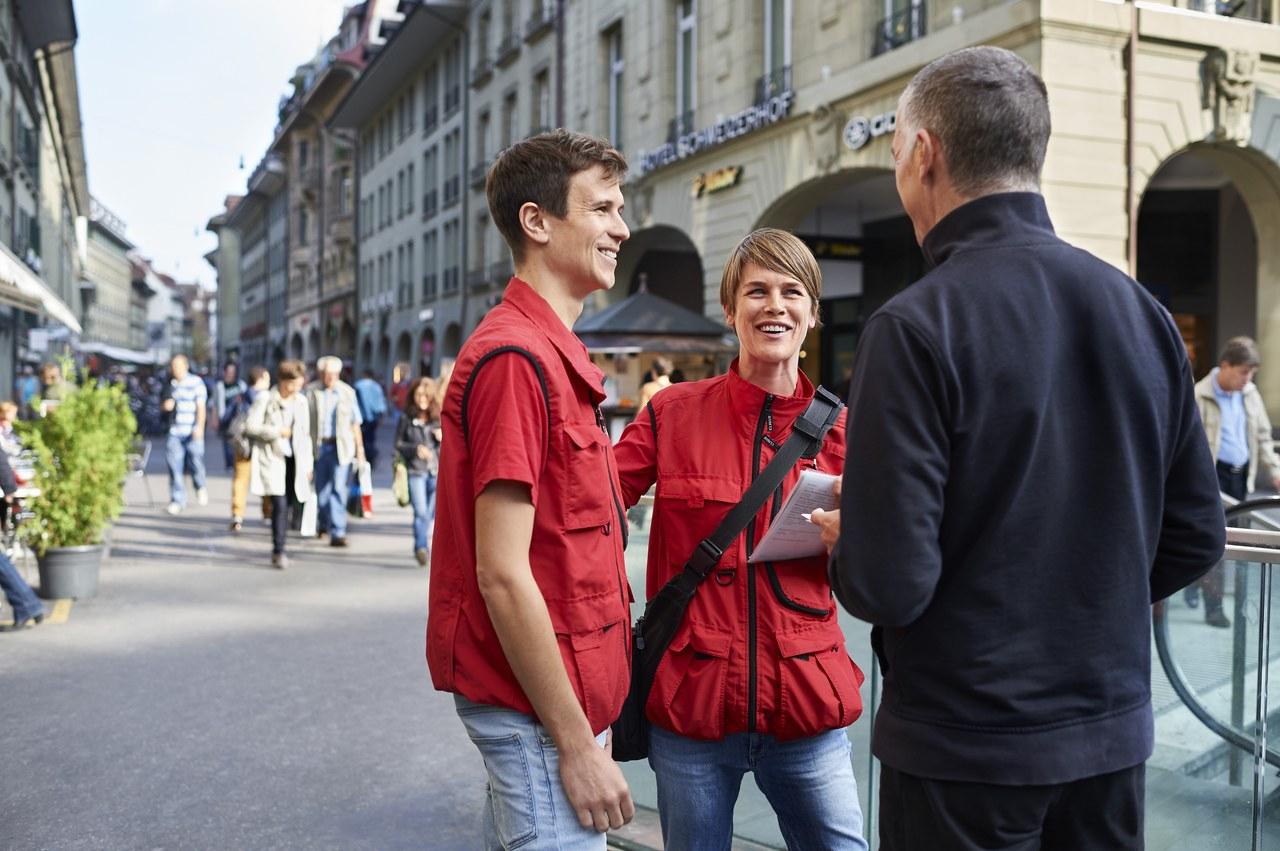 Eine Pinto-Mitarbeiterin und ein Pinto-Mitarbeiter im Gespräch mit einem Passanten.