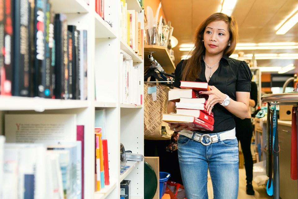 Frau trägt einen Stabel Bücher