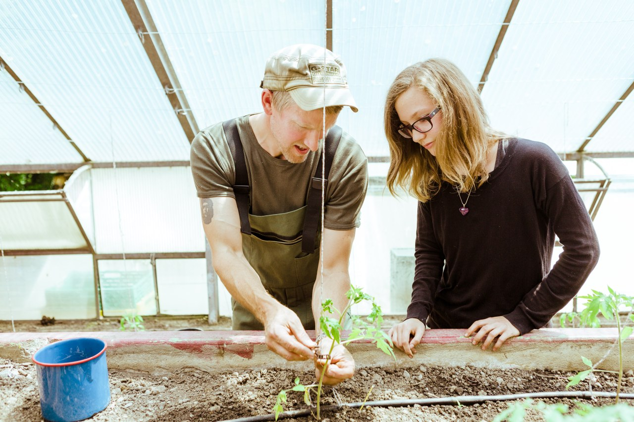 Jugendliche mit Fachleiter bei Gartenarbeit