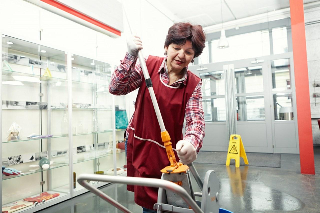 Bildsituation Frau putzt Eingang