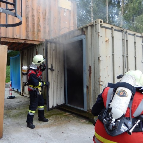 Angehörige der Feuerwehr vor dem Brandcontainer der Heissausbildungsanlage Bern. Vergrösserte Ansicht