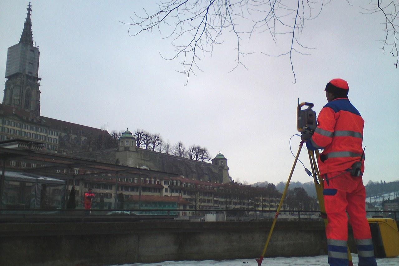 Person vor Vermessungsinstrument an der Aare mit Sicht zum Berner Münster