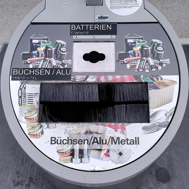 Sammelstellenbehälter für Büchsen und Batterien angeschrieben mit Brailleschrift und Keilschrift.