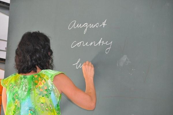 Frau schreibt Wörter an eine Wandtafel.