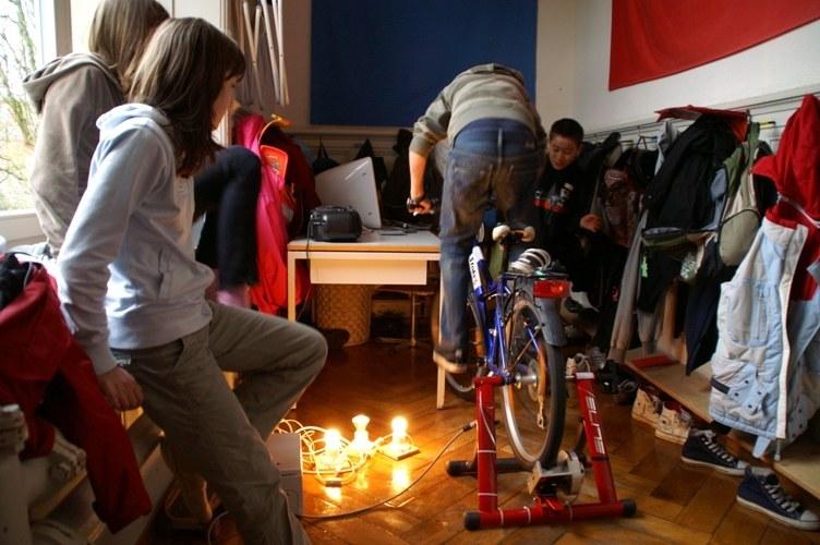Foto zeigt ein Fahrrad, das mit dem Hinterrad in einer Vorrichtung mit einem grossen Dynamo eingespannt ist. Durch die Tretbewegung wird elektrischer Strom erzeugt, der z.B. Lampen erhellt.