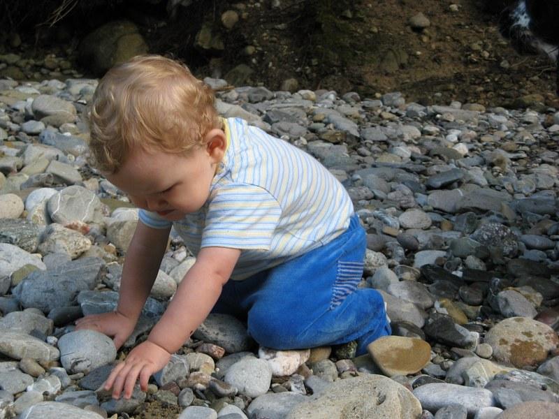 Kleinkind spielt mit Steinen.