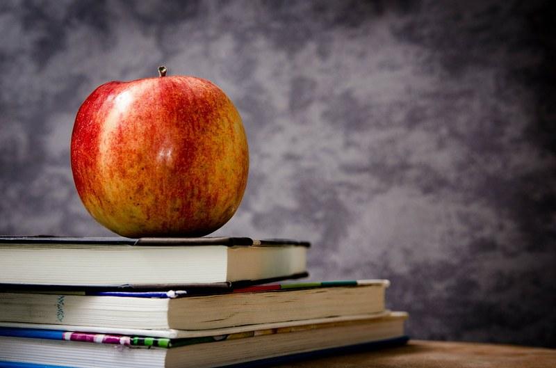 Ein Apfel auf einem Bücherstapel.