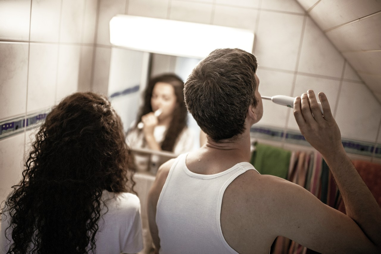 Eine Frau und ein Mann putzen sich voneinander abgewendet die Zähne