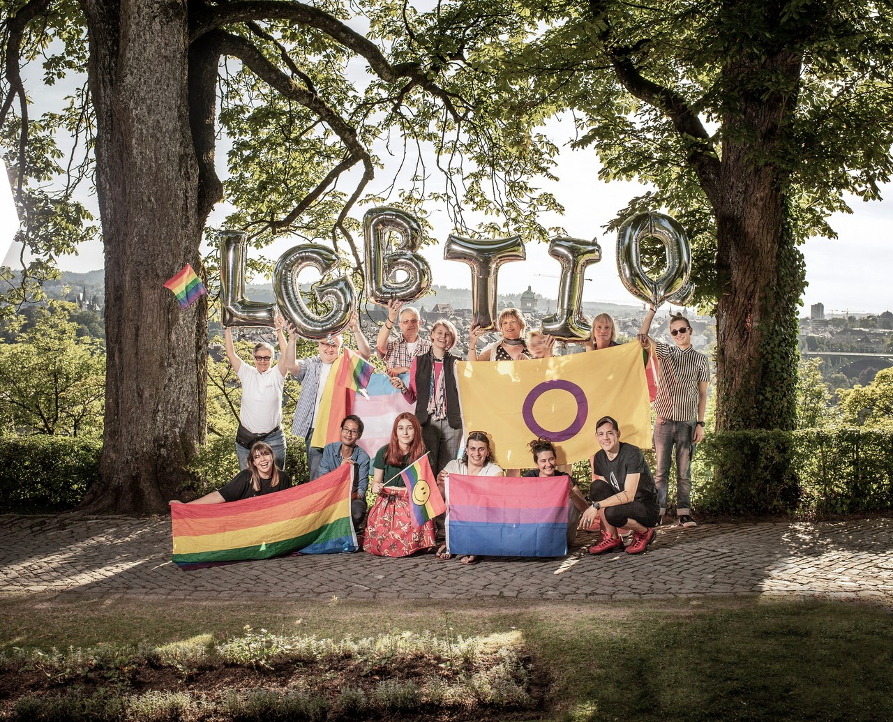 Eine Gruppe von LGBTIQ-Menschen mit LGBTIQ Buchstabenballons und Pride Flaggen