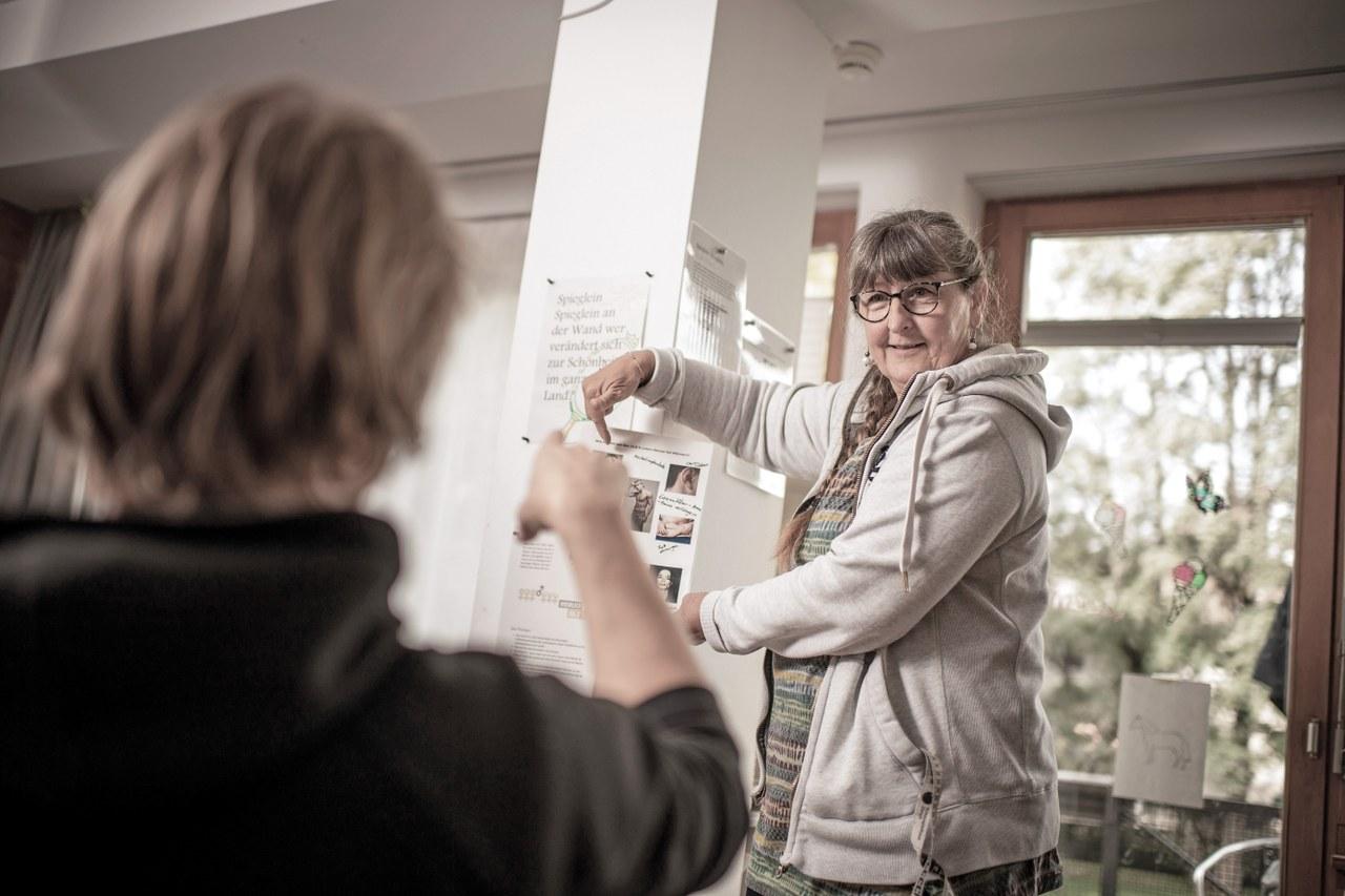 Eine Mitarbeiterin der Schlossmatt und ein Jugendlicher vor einer Gender-Wand