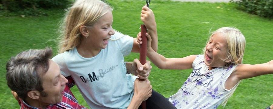 zwei Mädchen mit ihrem Vater auf einer Schaukel
